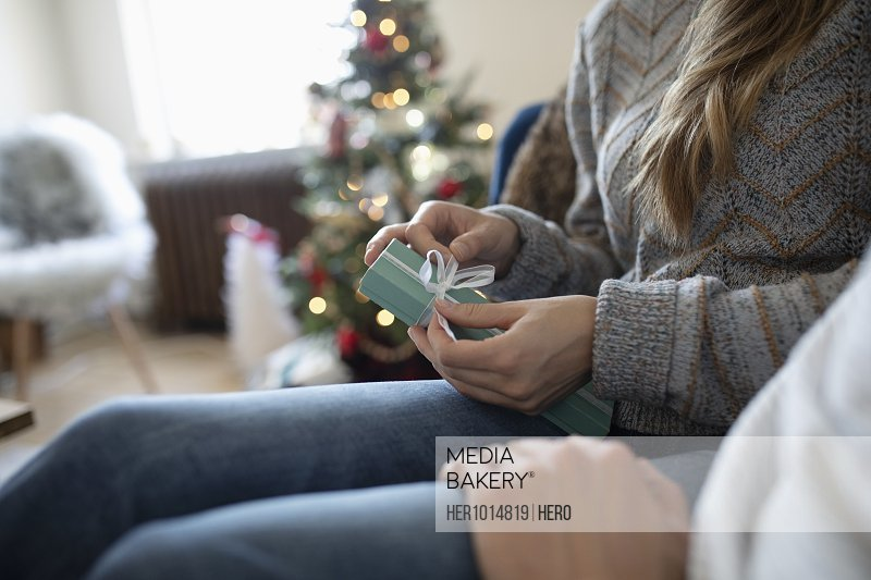 Young couple opening Christmas gift in living room