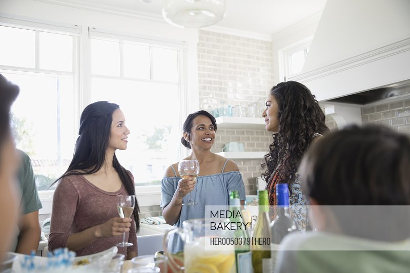 Women friends drinking white wine in kitchen