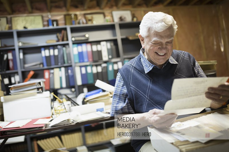 Smiling senior man reading old letters