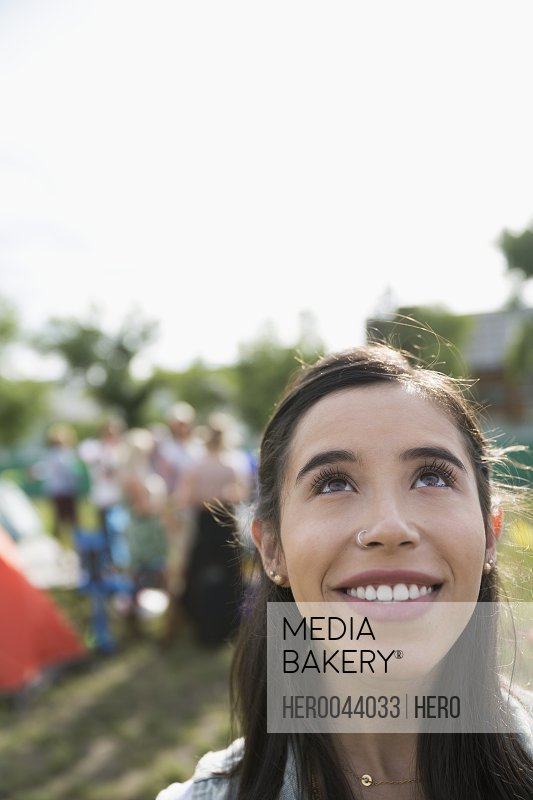 Portrait smiling young brunette woman looking up at summer music festival campsite