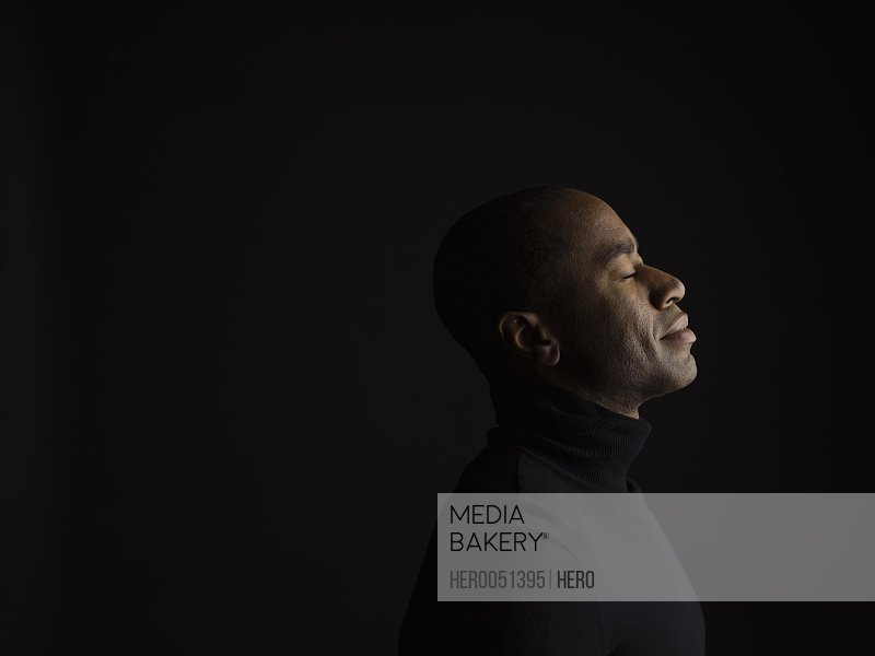Profile portrait serene African American man with eyes closed and head back against black background
