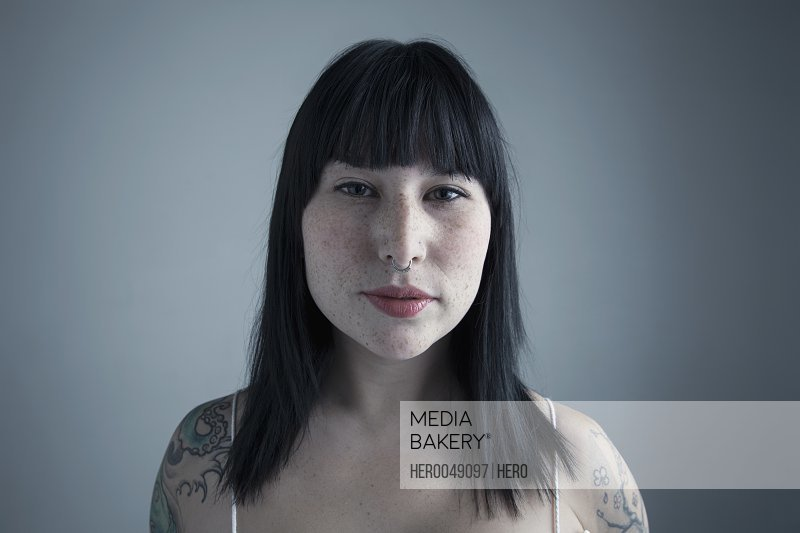 Portrait serious brunette mixed race young woman with tattooed shoulders