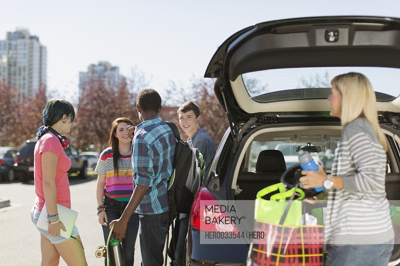 mom unloading supplies from hatchback for teenagers