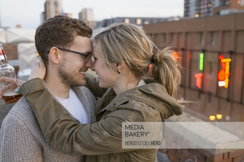 Couple hugging face to face on urban rooftop