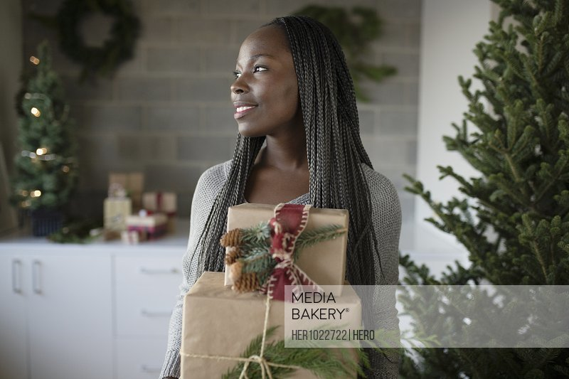 Smiling young woman carrying Christmas gifts