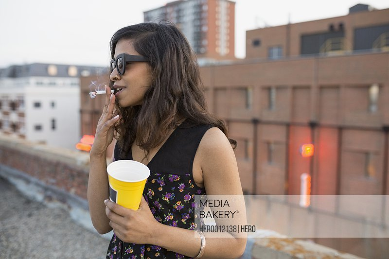 Woman smoking and drinking on urban rooftop