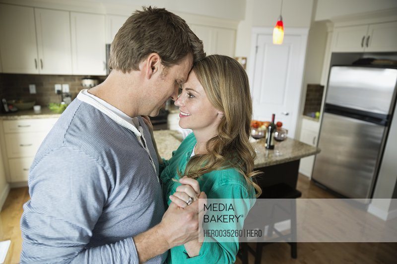 Side view of romantic mid adult couple dancing in kitchen