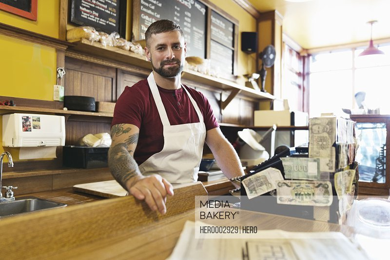 Portrait of male deli owner standing behind cash register
