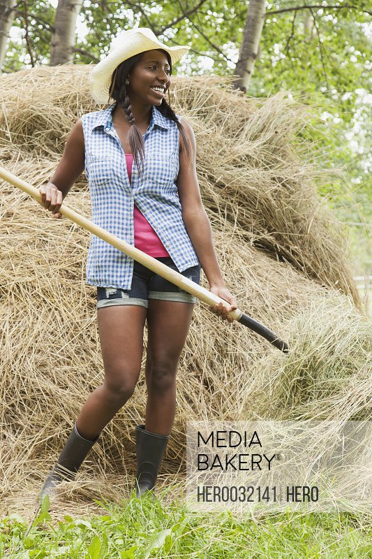 pretty african american woman using pitchfork to do chores