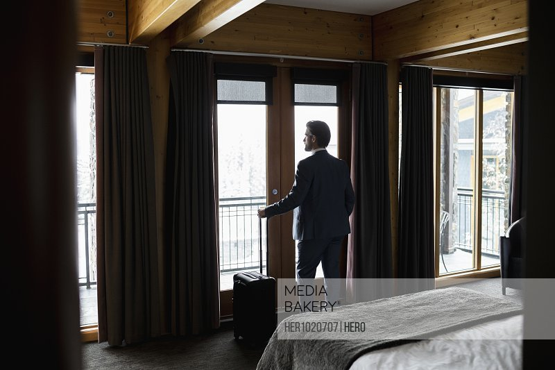 Thoughtful businessman with suitcase looking out hotel room window