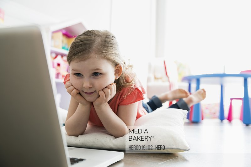 Girl using laptop on floor with pillow