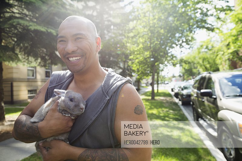 Smiling man with tattoos holding bunny in sunny grass