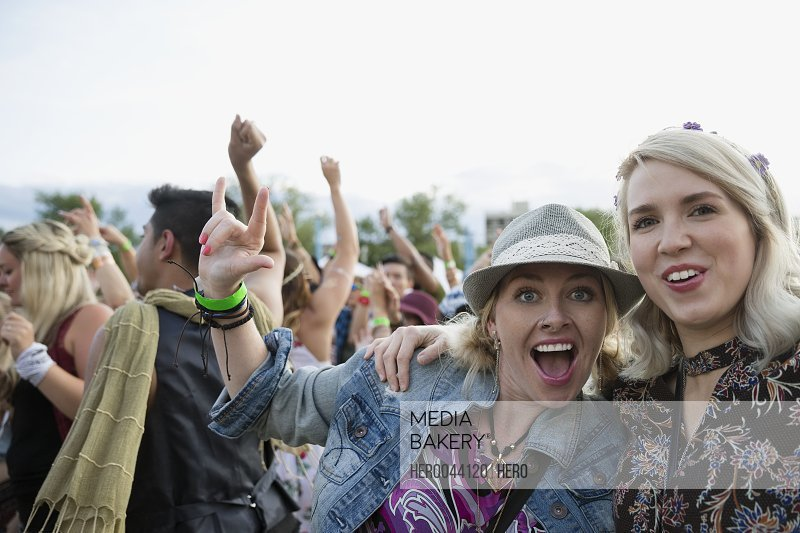 Portrait enthusiastic young women gesturing in crowd at summer music festival