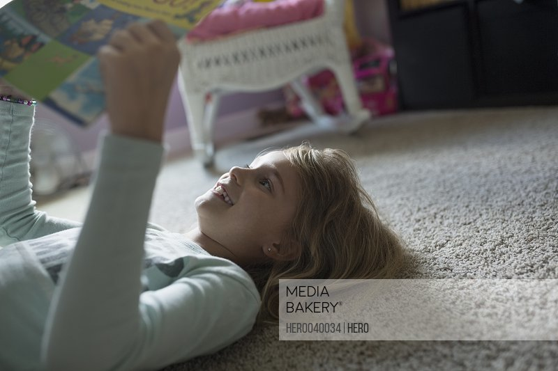 Girl reading book on bedroom floor