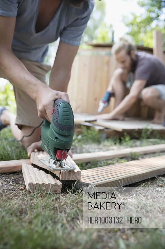 Man with power saw cutting wood planks