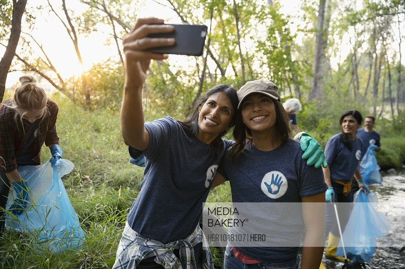Happy mother and daughter taking selfie and volunteering, cleaning up garbage in park