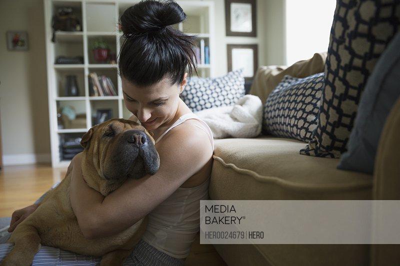 Woman hugging dog on living room floor