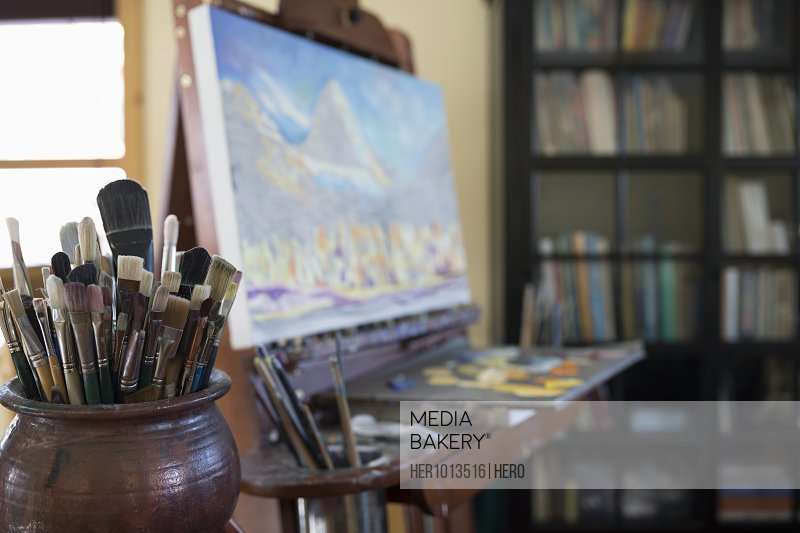 Paintbrushes in bowl in front of painting on easel