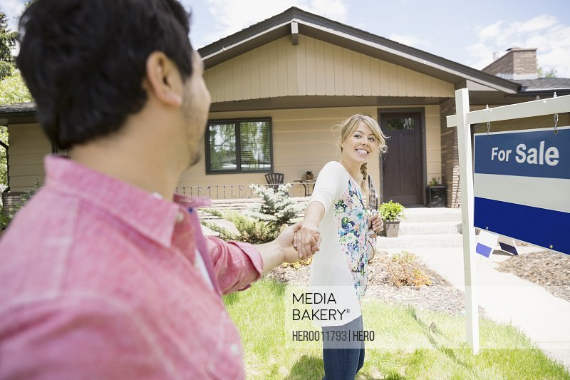 Couple holding hands outside house for sale