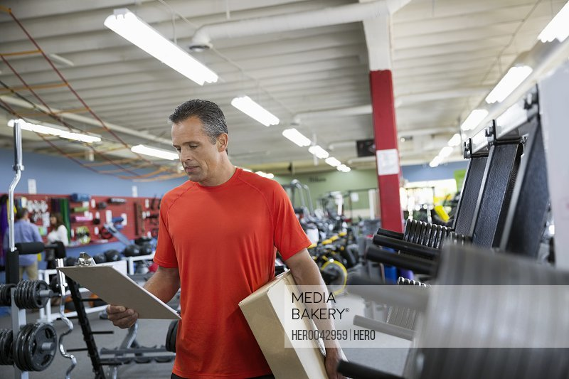 Worker with clipboard in home gym equipment store