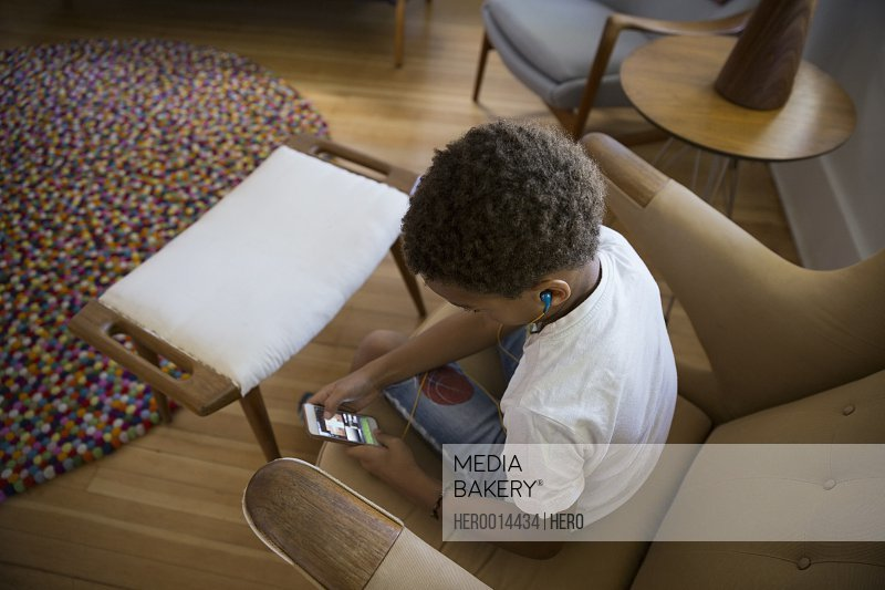 Boy listening to mp3 player in armchair