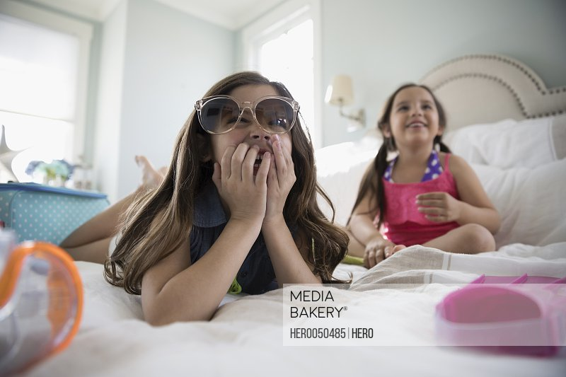 Smiling Latina sisters wearing sunglasses packing for vacation on bed