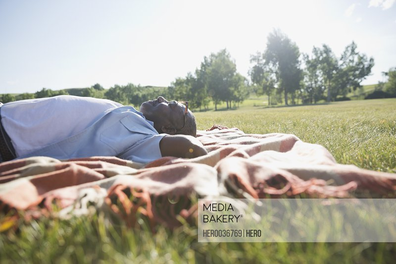 Side view of senior man lying on grass outdoors