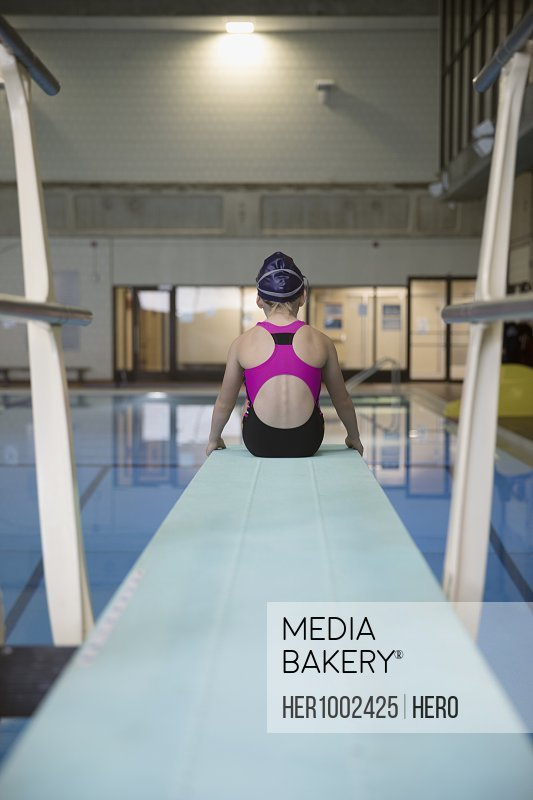 Girl swimmer sitting at the edge of springboard diving board over swimming pool