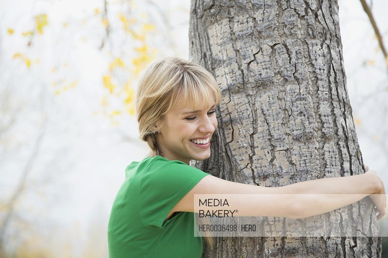 Happy young woman hugging tree
