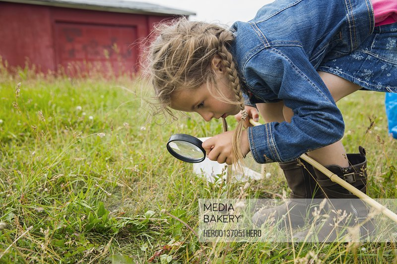 Curious girl with magnifying glass