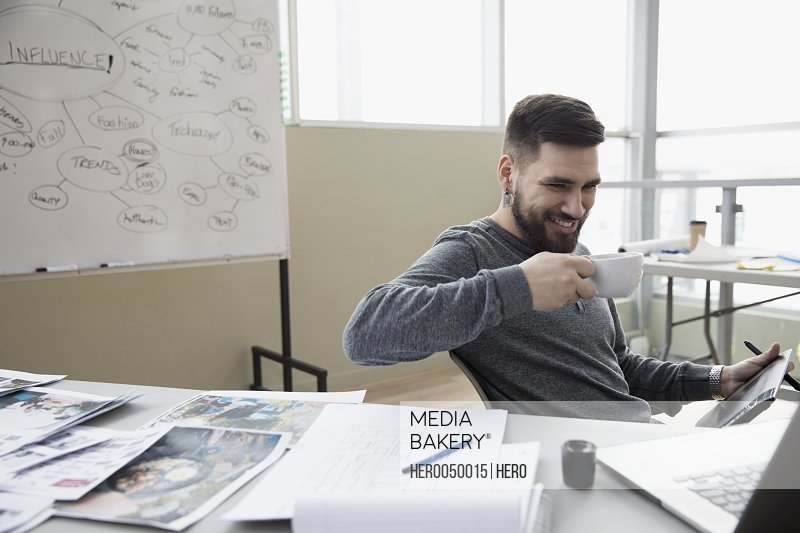 Smiling creative male designer drinking coffee and using graphics tablet in office