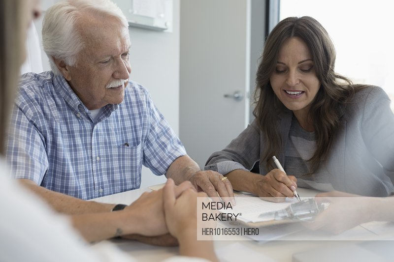 Female doctor reviewing paperwork with senior male patient in clinic