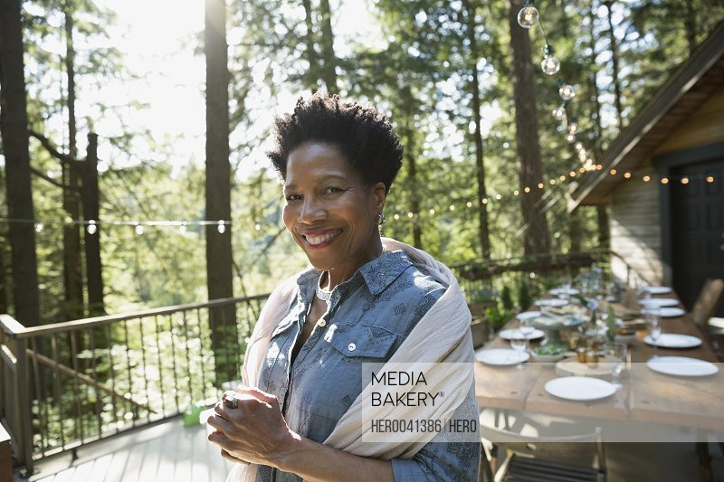 Portrait smiling woman on sunny cabin balcony in woods