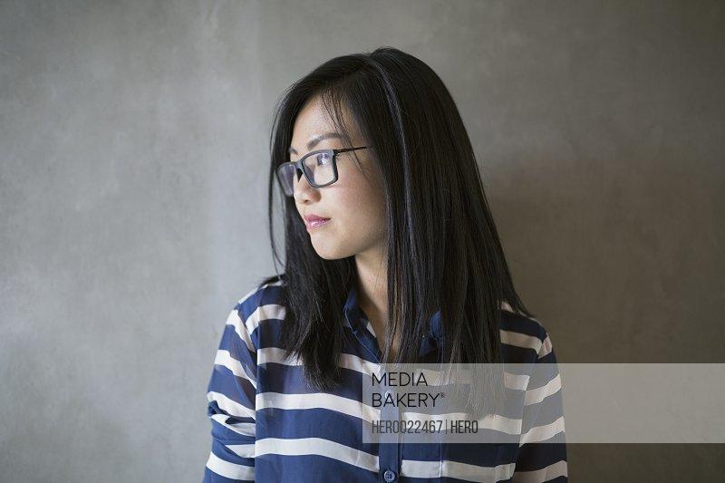 Pensive businesswoman black hair and eyeglasses looking away