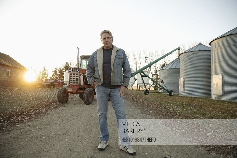 Portrait confident male farmer standing near silos on farm