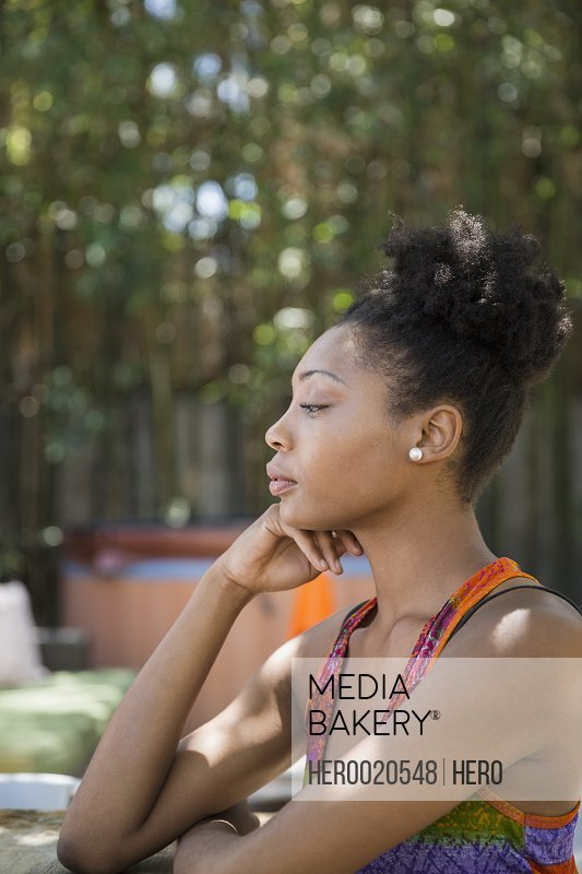 Profile of pensive woman sitting on patio