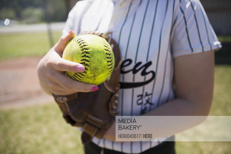 Close up middle school girl softball player holding fluorescent softball