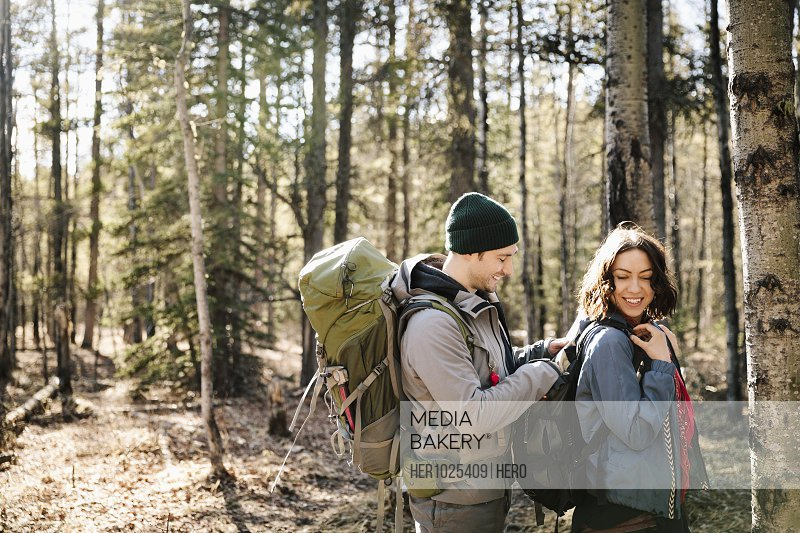 Couple with backpacks hiking in woods