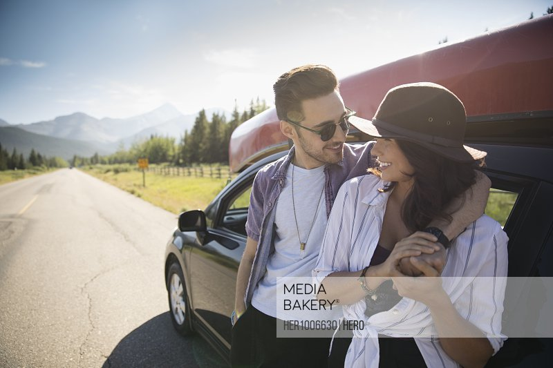 Affectionate young couple hugging outside car on sunny rural roadside, enjoying summer road trip