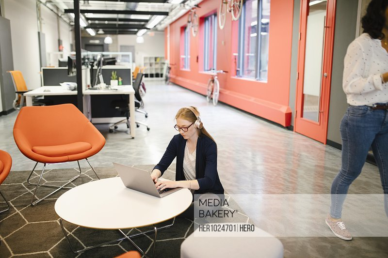 Creative businesswoman with headphones using laptop in coworking space