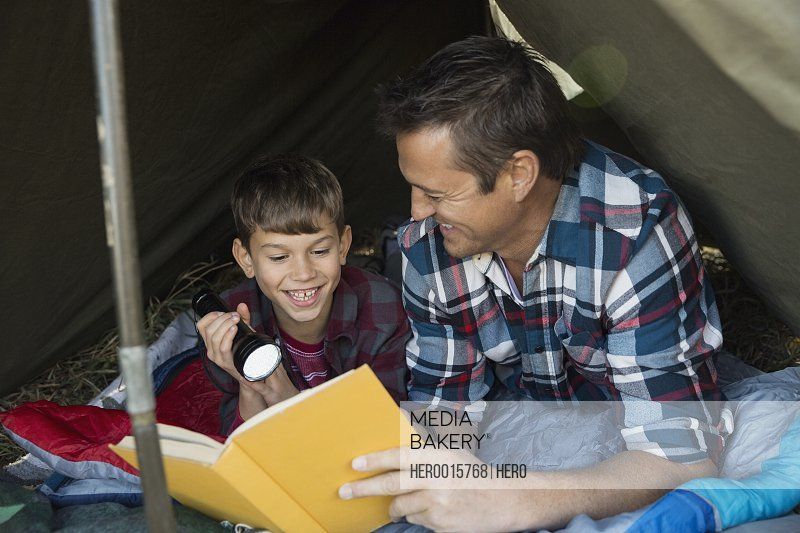 Father and son reading book inside tent