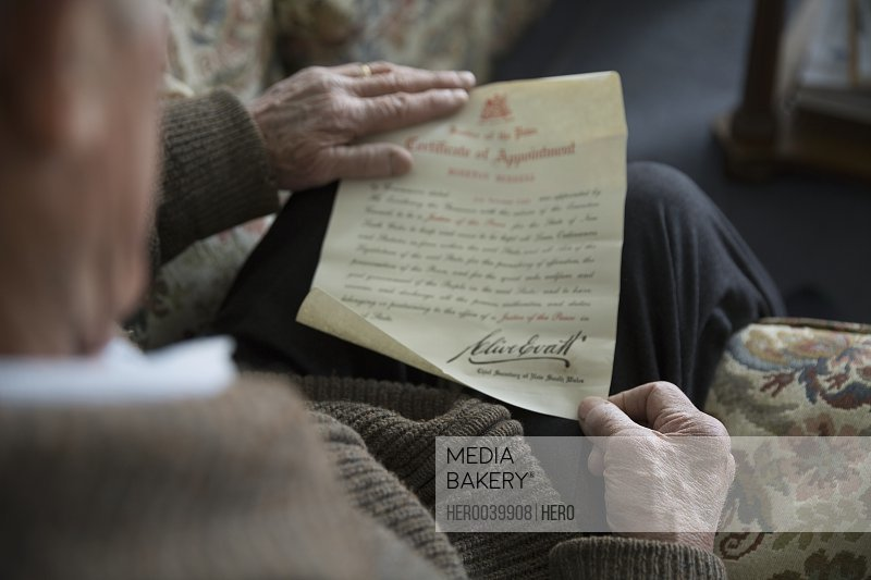 Senior man reading old military certificate of appointment letter