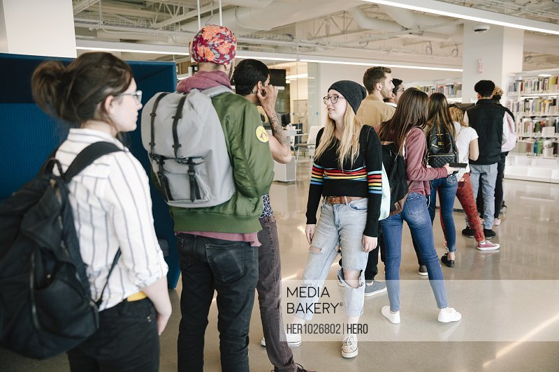 Students standing in university library talking