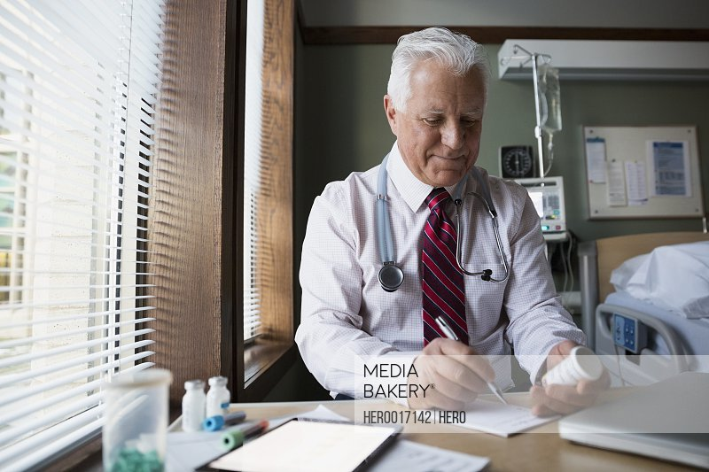Doctor writing prescription in hospital