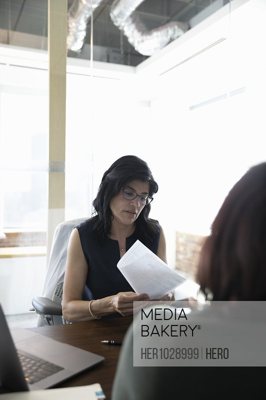 Businesswoman holding letter in meeting with colleague