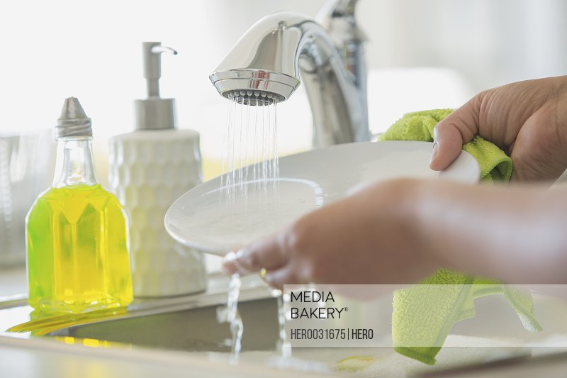 Woman rinsing white plate in kitchen sink