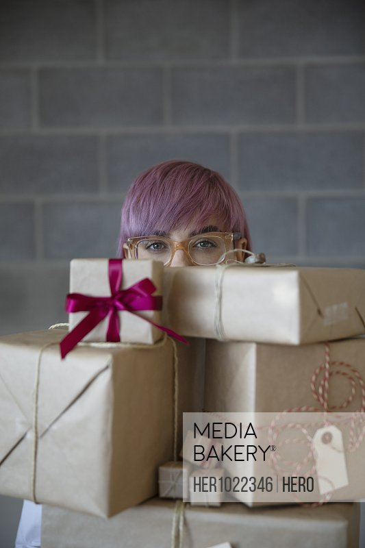 Portrait non-binary gender person carrying stack of Christmas gifts