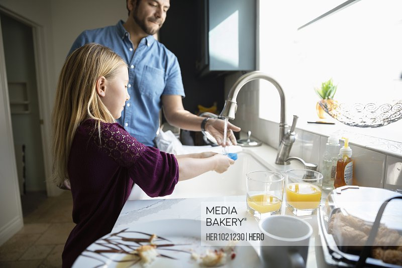 Latinx father and daughter doing dishes at kitchen sink