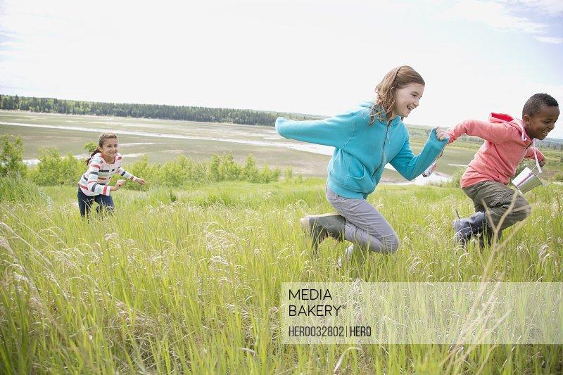elementary aged children running in grassland