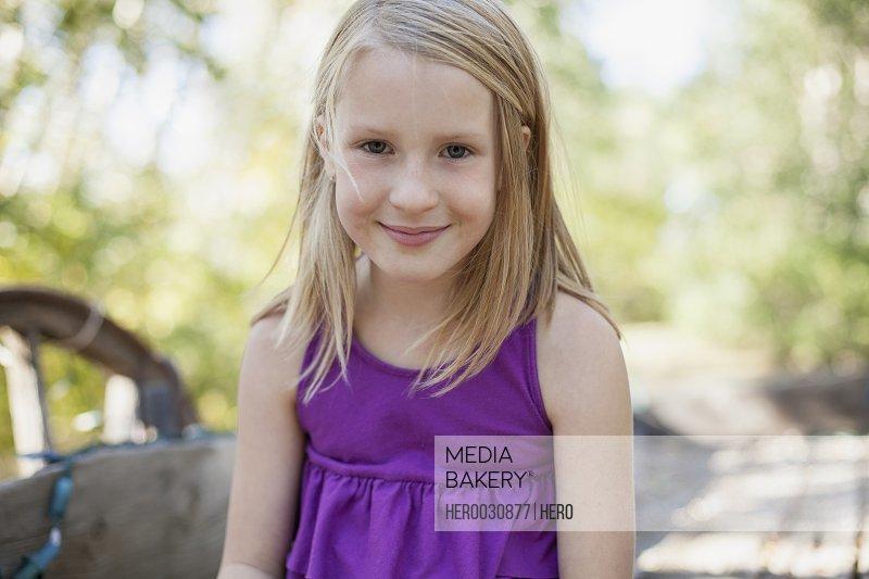 Portrait of cute blond girl in purple shirt